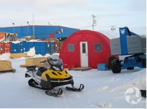 A snowmobile parked in front of a Parcoll tent, with shipping containers and a building in the background.