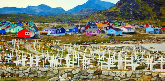 The vividly coloured houses of Nanortalik are seen between the white crosses of a cemetery in the foreground and a mountain range in the distance.