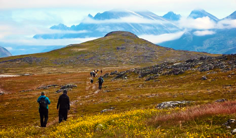 Hikers climb a path up a mountain on the island of Unatoq, Greenland. Clouds cover the high mountain peaks in the distance.