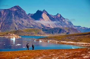 Rugged mountains of Greenland with two hikers standing near the water's edge.