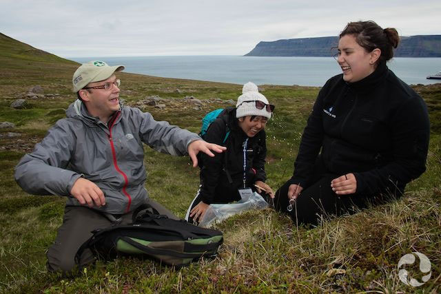 A man and two teenage girls talk, on their knees on the ground in Iceland.