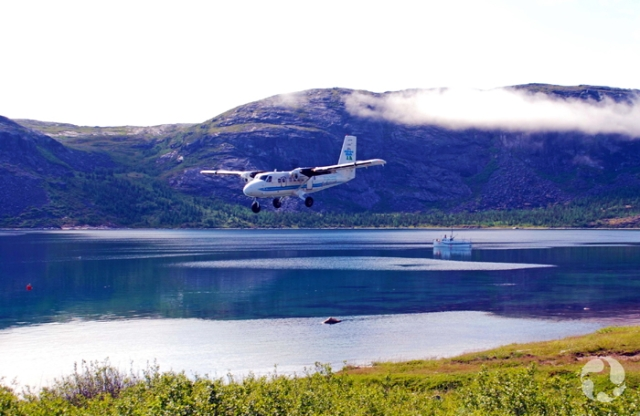 A small plane over water with hills and a ship in the background.