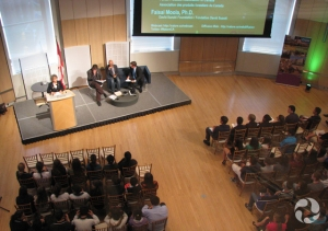 Overhead view of an expert panel and audience in the museum salon.