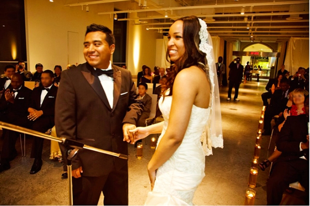 Bride and groom smiling and holding hands during the ceremony.