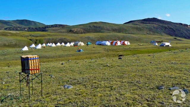 About 20 tents and Quonset huts, and a helicopter are grouped on the tundra, on Victoria Island, NWT, in the Arctic.