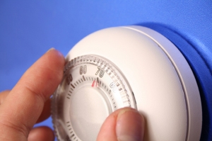 A hand adjusts a thermostat.