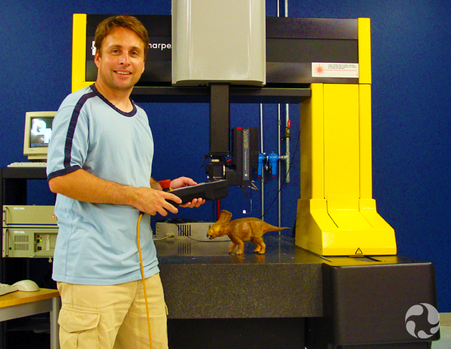 Paul poses beside the Coordinated Measuring Machine, with a small model of Vagaceratops irvinensis under the scanner.