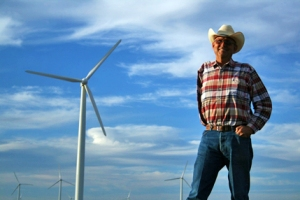 A man stands on a wind farm, with windmills in the background.