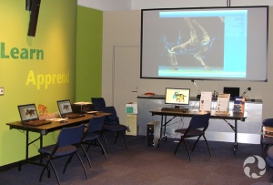 Laptops on tables and a large projection screen in the museum.