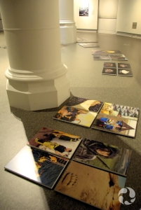 Mounted images for the exhibition lie on the floor by the wall on which they will hang.