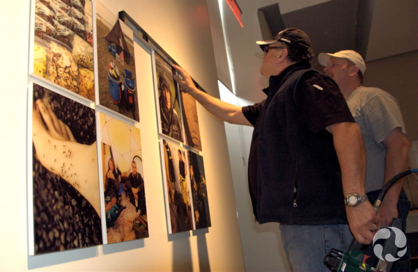 Two men check the level and spacing of mounted images that they are hanging.