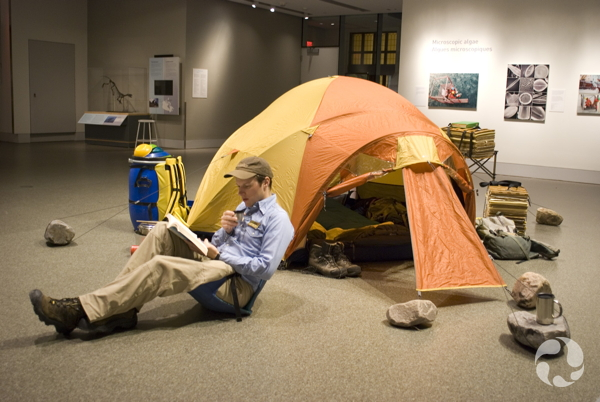 In the midst of the Awesome Arctic exhibition, Roger Bull sits on a camp chair before a tent, some rocks and plant presses.