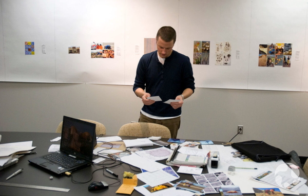 Roger Bull stands at a table covered with photographs, papers and a laptop.