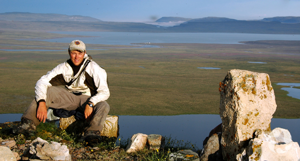 Roger Bull sits on a rock overlooking a landscape below of tundra and water.