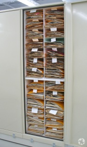Herbarium cabinets, one of which is open to reveal stacks of herbarium sheets.