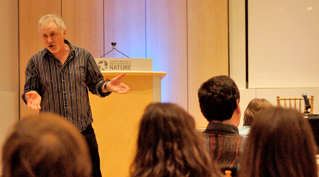 Professor Aaron Doyle standing in front of an audience in the Salon of the Canadian Museum of Nature.