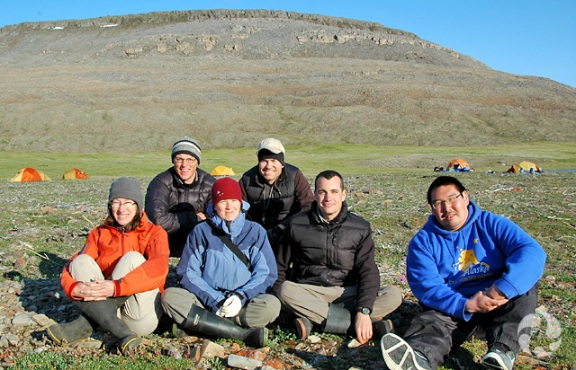 Six people sit on tundra with their tents and a hill visible in the background.