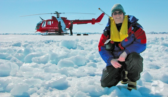 Researcher Michel Poulin crouching on snow with a helicopter in the background.