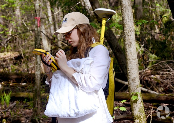 A woman wearing portable GPS equipment in a forest.