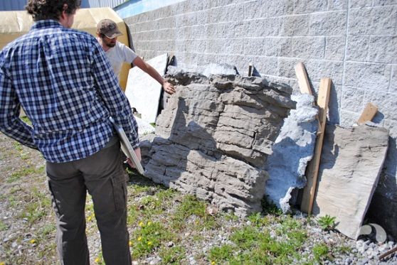 Two men look at rock samples outside a building.