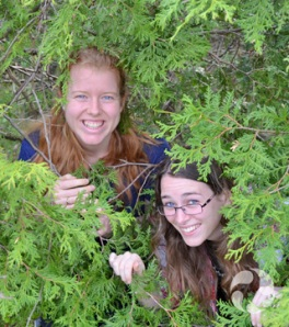 Emma Lehmberg and Cassandra Robillard peek from behind branches of an evergreen.
