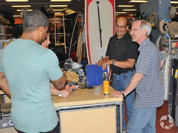 Two salespeople and two clients discuss merchandise in a sports equipment store.