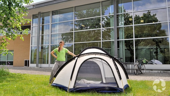 A woman stands beside a tent set up outside the museum's research and collections facility.