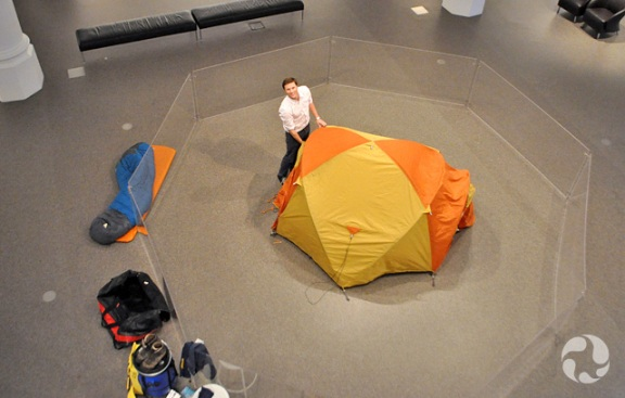 Overhead view of a man striking a tent in a gallery at the museum.