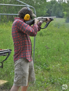 A man aims a shotgun in a field.