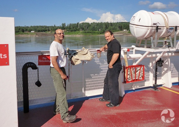 Two men standing by edge of ferry with river in background.