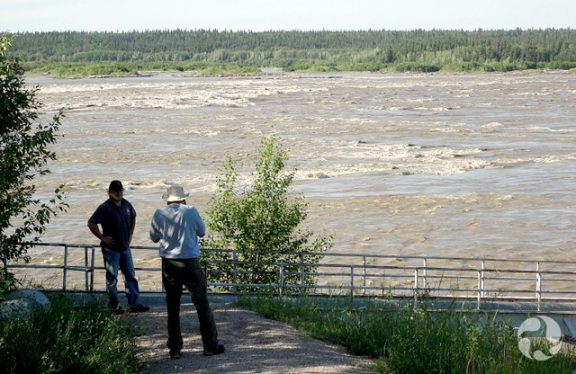 Two men stand on riverbank looking at a set of rapids.