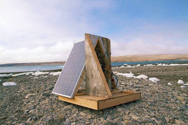 A solar panel and part of their platform on a rocky beach.