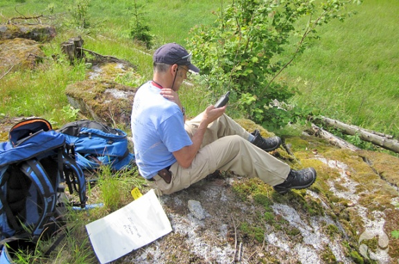 Man sitting on ground looks at GPS device in his hand.