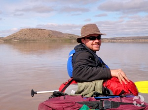 Man sitting in canoe with hill in the background.