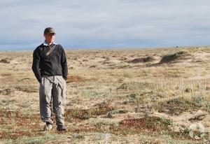 A man standing among sand dunes.