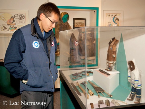 A teenager looks down at glass case containing artifacts.