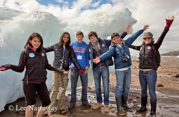Six teenagers stand with arms outstretched in front of large chunk of ice.