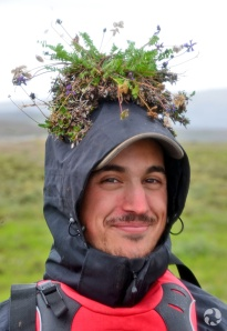 A man with a plant specimen balanced on his head.