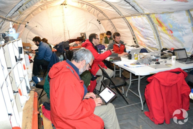 Man sitting with laptop in foreground, and others sitting at tables inside large tent.