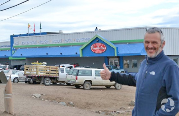 Man holding his thumb up with Tim Hortons store in background.