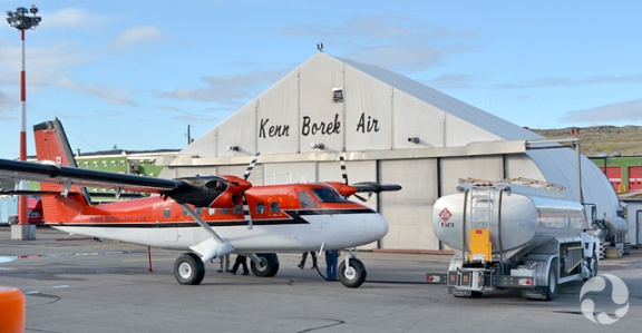 Small red plane in front of airplane hangar.