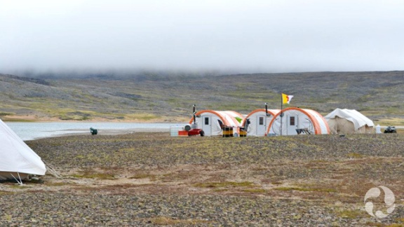 Four half-domed shelters on flat terrain.
