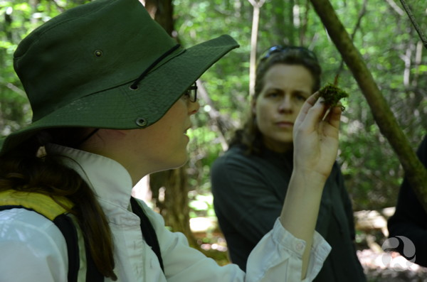 Two women look at a moss specimen that one is holding.