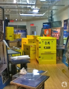 Shipping crates and exhibition panels in a large room.