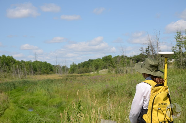 A woman with a pack on her back looks at the landscape.