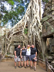 Four people stand in front of a stone building overgrown by the roots of a tree.