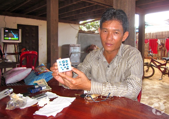 A man at a table displays a box of blue stones.