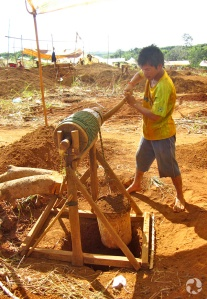 A man winches a bucket of earth from a narrow hole in the ground.