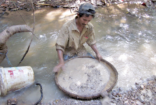 Zircon miner cleaning a bucket of mud from one of the holes at the Bo Loei mining area, Ratanakiri province, Cambodia. Image: Paula Piilonen © Canadian Museum of Nature