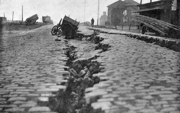 Low-angle view along a crack in the road that has swallowed a wagon.